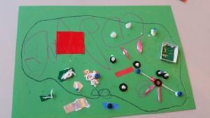 Rechtsonder is een poppetje en datheeft een bedje en het gaat met het vliegtuig naar het rode huisje om een boek te lezen