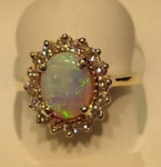 XXXCluster Diamond and Opal ring in a 14 kt. gold setting. Opal glows in pink, yellow, green and opaque color. $725