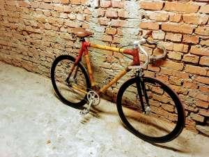 single speed z bambusa przy ceglastym murze