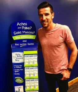 Soccer player Sebastien Le Toux at Boiron headquarters standing next to a display of Arnicare products.