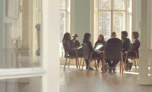 Åtta personer samtalar, sitter på stolar i en ring (utan bord) vid stora fönster i ett ljust rum.