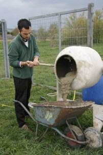 Ivan füllt die nächste Scheibtruhe mit frisch gemischter Beton.