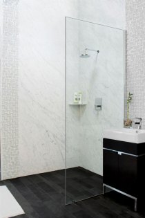 Bianca Carreaa Bolder Panels installed in a shower in the Stone Source - Tile Source International showroom. Includes the Bianco Carrera corner caddie and lava black slate on the floor
