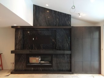 Livingstone fireplace during construction, featuring Ancient Woodgrain Bolder Panels, ample storage, TV wiring and new fireplace insert
