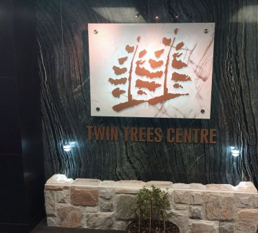 Twin Trees Centre entrance with Ancient Woodgrain Bolder Stone Panel and Xilo Bolder Stone Onyx Panel