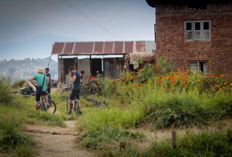 Băieții pe bicicletă pe-o cărare într-un sat