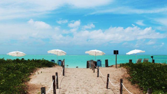 O caminho de areia para praia do Morro, com um mar verde claro e um céu azul.