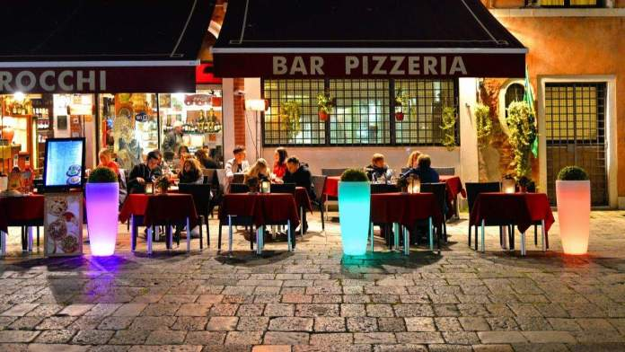 Pessoas no restaurante e pizzaria, ao ar livre, em Veneza, Itália