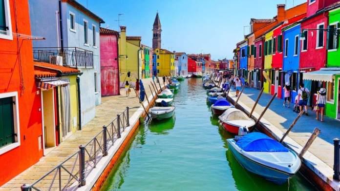 Casas venezianas coloridas, ao longo do canal nas ilhas de Burano, em Veneza, Itália.