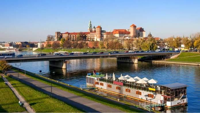 Rio Vístula, Ponte Podwawelski e um restaurante na barcaça no outono ao pôr do sol em Cracóvia - Polônia