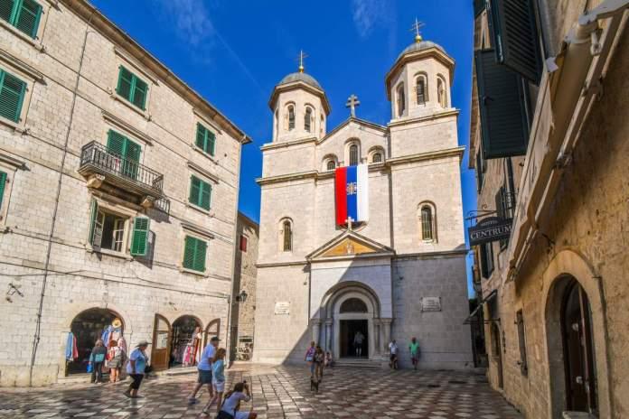 Turistas na frente da Igreja Nicholas, uma Igreja Ortodoxa Sérvia no centro da cidade velha de Kotor, Montenegro.