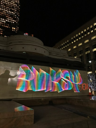 Banksy Style Luma Paint Public Light Graffiti as Lightpainting, London Winter Lights, Canary Wharf, 2017