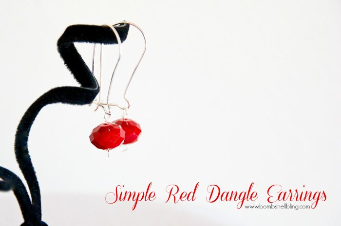 red dangle earrings on display stand