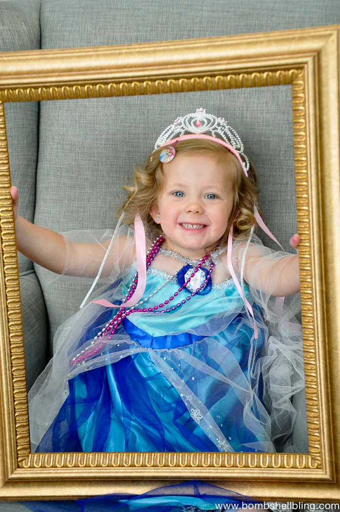 Girl in blue dress holding gold frame at Bippity Boppity Boutique Party
