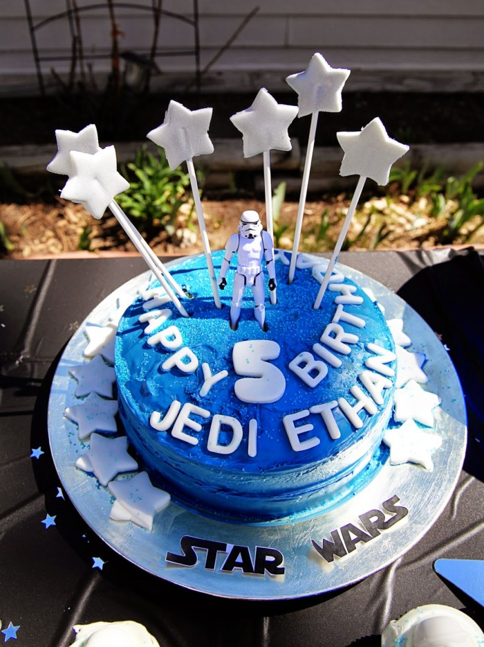 Star Wars Lego birthday cake with white star candles and Storm Trooper toy for topper