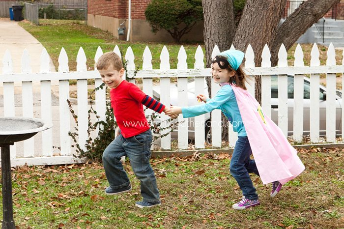 Boy and Girl holding hands running together outside at superhero birthday party