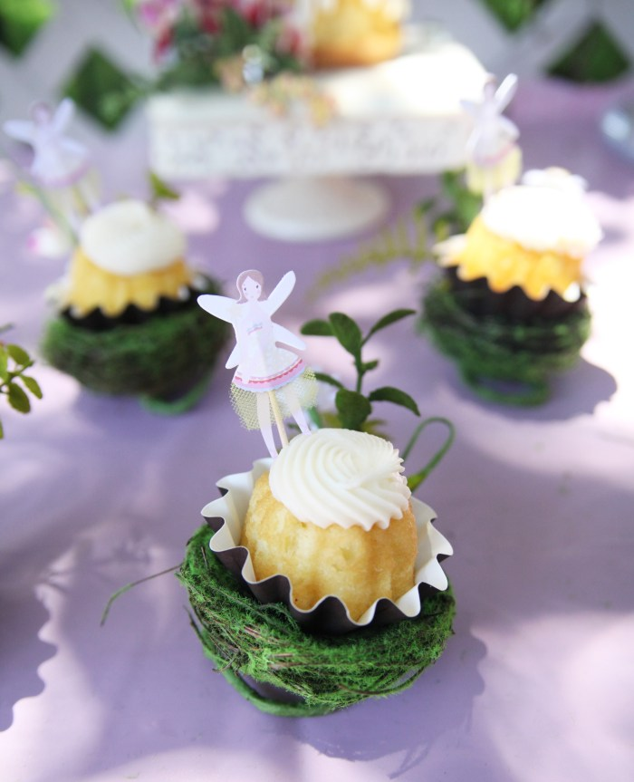 Vanilla cupcake in moss bird's nest on table at fairy birthday party