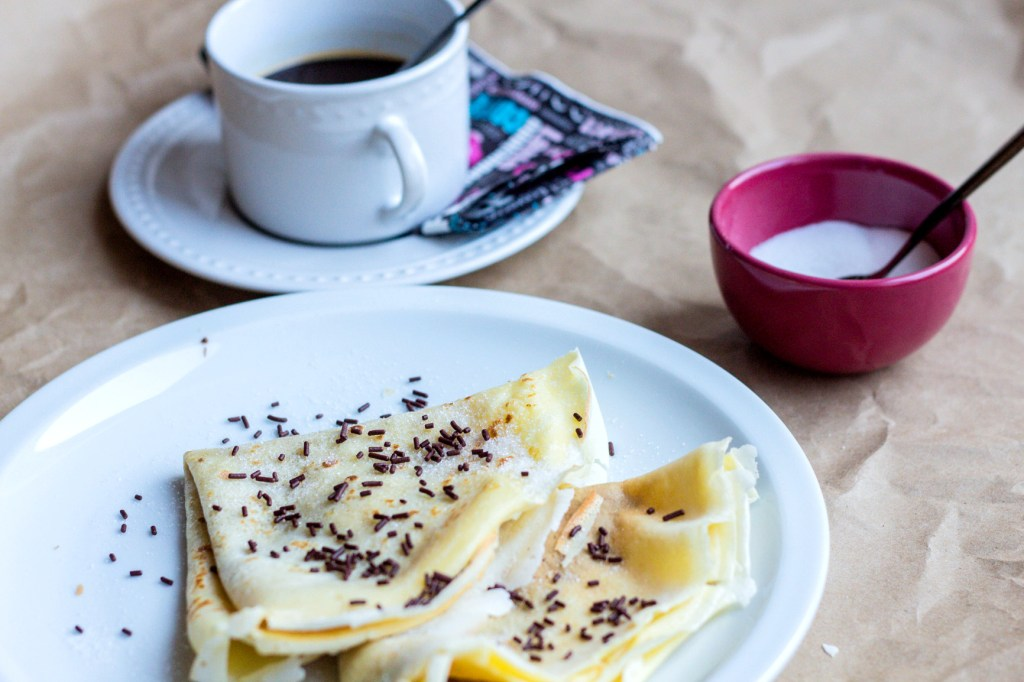 2 crepes folded with chocolate sprinkles with a cup of dark coffee on the side and a ramekin of sugar.