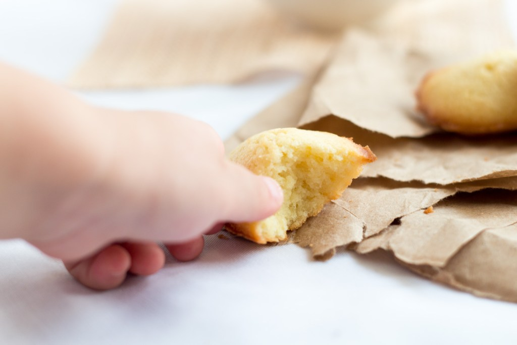Madeleine Recipe: little hand grabbing a madeleines already bitten.