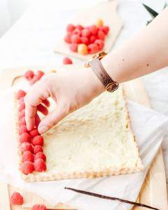 Hand placing raspberries on the french vanilla pastry cream tart