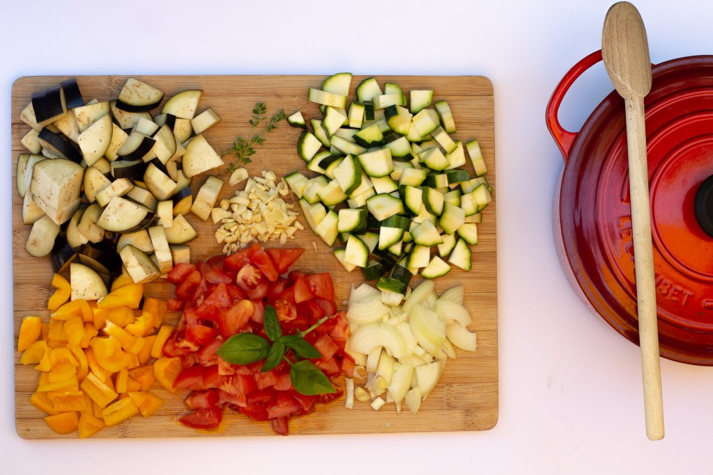 Wood chopping board with all the ingredients diced for ratatouille