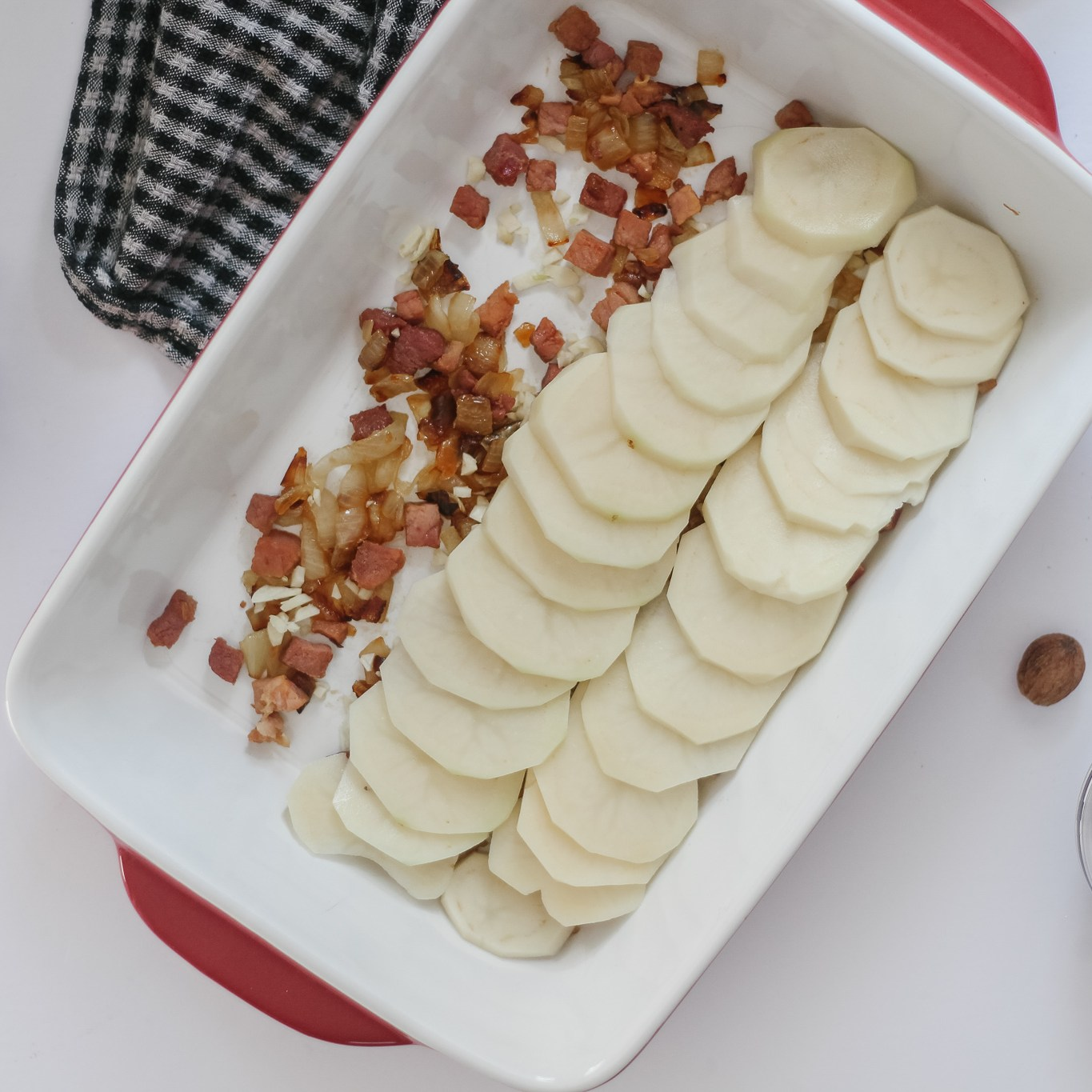 Building the scalloped potatoes dish:Thinly sliced potatoes on ham and onion