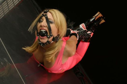 Gorgeous Young Blonde in Latex Gets Tape Bound, Gagged and Harnessed