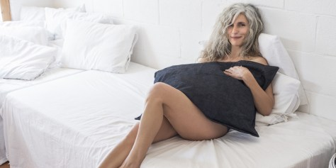 mature woman with black pillow on white bed
