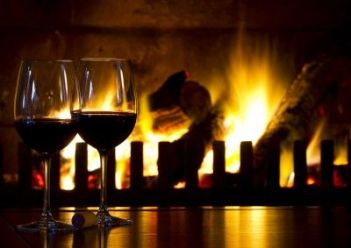 Two glasses of wine by a cosy open fire