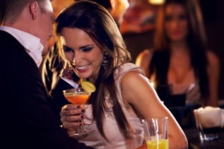 Man and woman in bar drinking cocktails, laughing