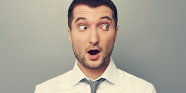 Man in shirt and tie looking surprised and to the left