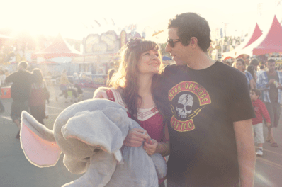 A couple at a theme park, with the girl holding a toy