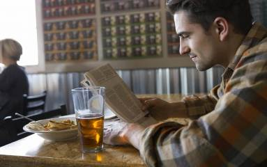 Man dining alone reading newspaper