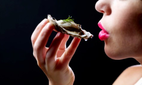 Woman reaching to eat oyster, close-up
