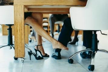 Woman playing footsie underneath work desk