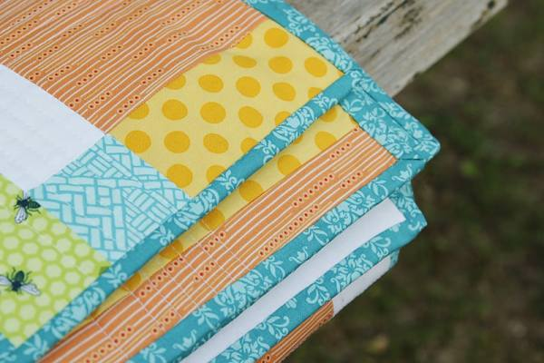 Spring Baby Quilt by Bonjour Quilts, a disappearing 9 patch pattern with an applique back detail. Free pattern download.