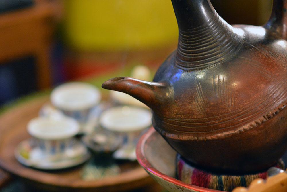 Tonkrug im Vordergrund, Kaffeetassen im Hintergrund