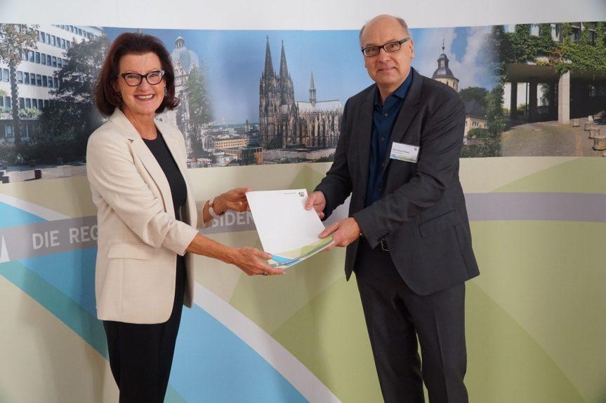 Regierungspräsidentin Gisela Walsken überreicht den Förderbescheid an Bonns Stadtbaurat Helmut Wiesner.