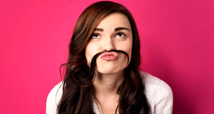 A pretty girl using her long hair as a moustache