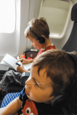 two kids sitting on a plane with headphones on doing activities flying with kids