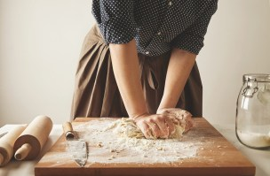Woman kneads dough for pasta on wooden board near two rolling pins and jar with flour