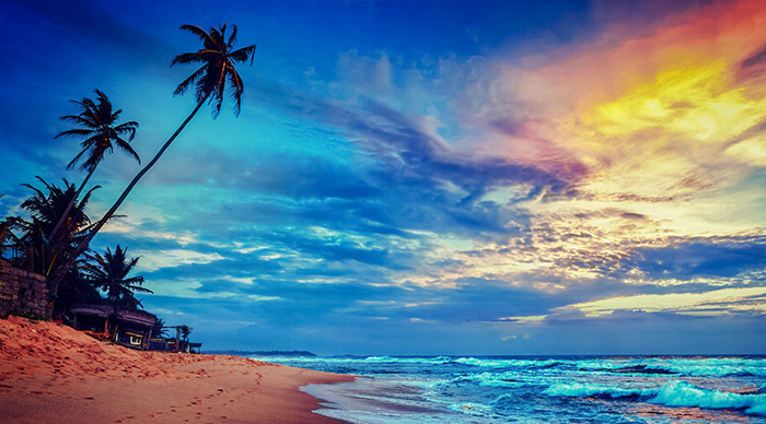 Image of sunset on tropical beach with dramatic cloud sky in Sri Lanka