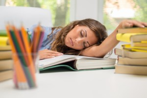 Portrait of beautiful tired teenage girl sleeping on the books in the library.