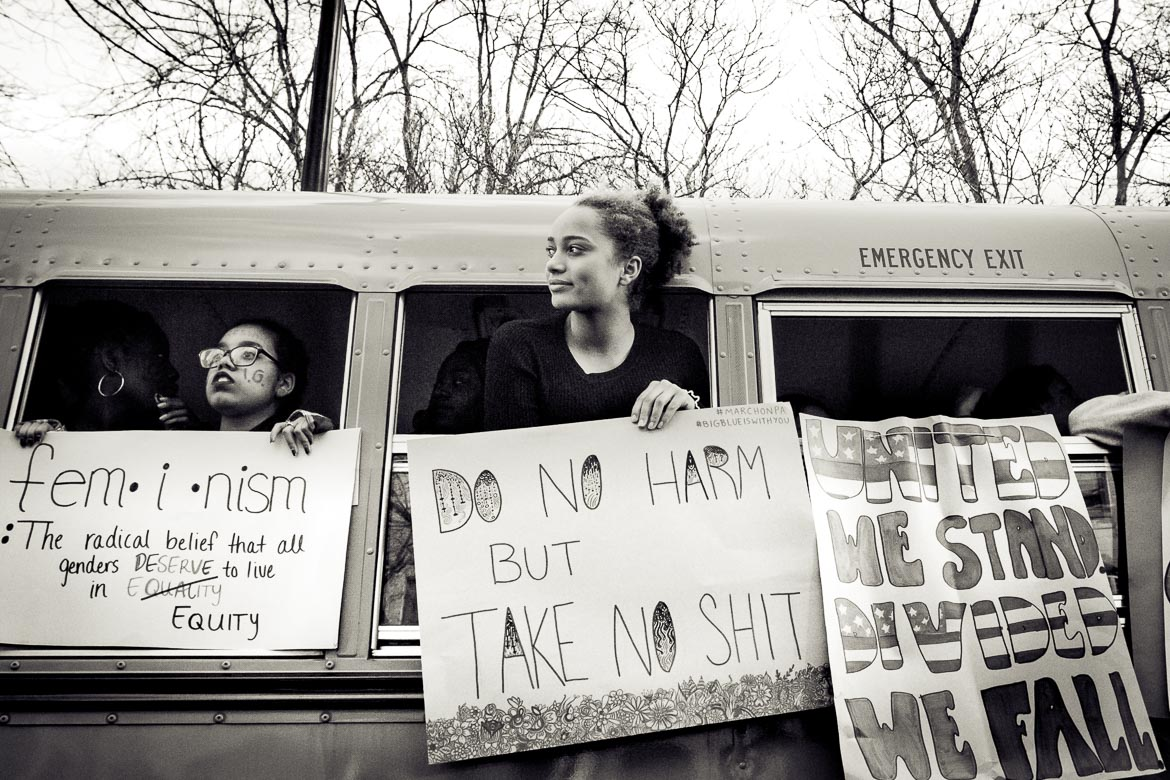 Teenage girl in school bus holding protest sign