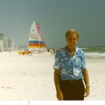 Author's dad standing on white sandy beach with colorful sailboat parked on sand in background.