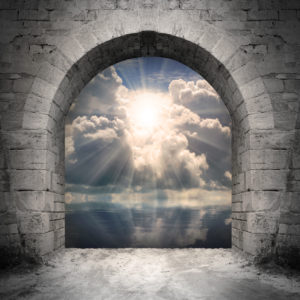 stone portal with intense light shining through clouds on the other side of the portal.