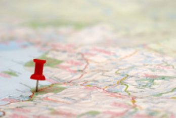 Map with a push pin stuck in a specific location, symbolizing road map to a goal.
