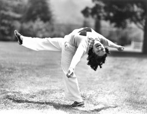 Smiling woman, standing on one foot, almost doing a back bend.