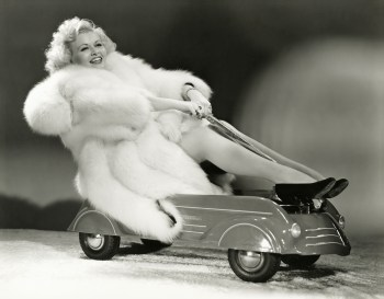 Vintage black and white photo of a woman in fur riding a kiddie car.