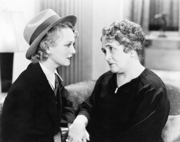 Vintage black and white photo of two women discussing romance based on ownership of their large-cap, mid-cap, and small-cap stocks.